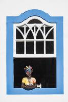 Traditional brazilian souvenir girl at the country house window in historic town Paraty, Rio de Janeiro state, Brazil