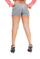 Woman standing from back in shorts with long legs