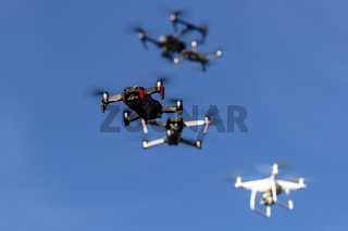 A Group Of Drones Fly Together Through The Air Against A Blue Sky