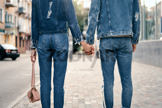 Couple holding hands in city street