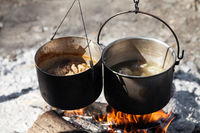 Cooking in two sooty old pots on campfire
