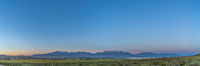 Scenic panoramic view of the valley lake and snow peaked mountain under blue sky