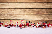 Santas in front of wooden wall