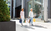 senior women with shopping bags walking in city
