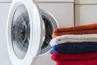 Laundry service, housework, washing machine and a stack of colorful towels.
