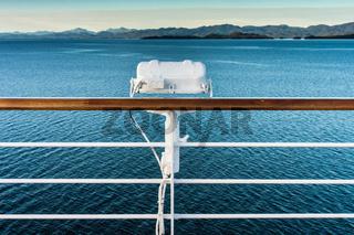White metal exterior light fixture on railing of cruise ship, Alaska Inside Passage route.