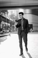 Young happy Hispanic businessman using phone outside the office building in black and white