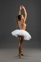 Ballet dancer topless and barefoot rearview