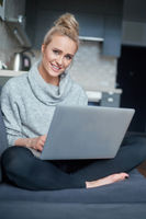 Cheerful young blond woman sitting on couch in living room and using laptop