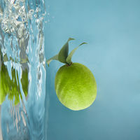 Round green lime with leaves in water on a blue background