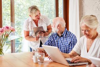 Sozialarbeiter hilft Senioren im Computerkurs