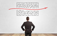 Businessman looking to a maze on a wall