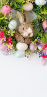 easter wreath with colorful eggs and flowers and a rabbit in the center