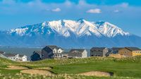 Panorama frame Houses on a grassy hill with view of lake and snow peaked mountain
