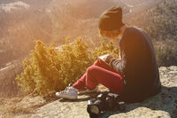 Portrait of a hipster designer photographer girl in hat and sunglasses draws a pastel in her notebook sitting on a rock outdoor in the mountains. The concept of a free freelancer artist