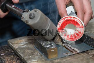 Handarbeiter erlernt mit Loetkolben und Loetdraht loeten - Nahaufnahme