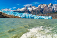 Natural landscape at Glacier Grey with the snowy rock mountain, Lake Grey and water splash