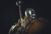 Vintage Viking, Scandinavian warrior with helmet and war paintings, wears a sword and a cape of animal skin