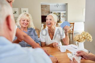 Senior Frau gewinnt beim Karten spielen