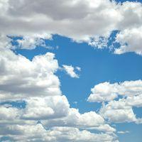 Puffy cumulus clouds on dazzling blue sky