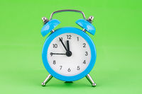 Classic alarm clock on a green background