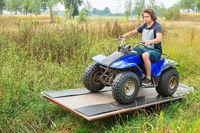 Young european man driving quad on balance