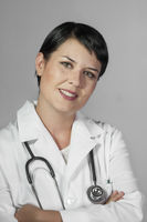 Portrait of an attractive young female doctor in white coat. Smiling medical woman doctor. Isolated over white background