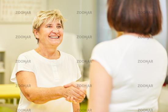 Lächelnde Senior Frau begrüßt Therapeutin oder Ärztin