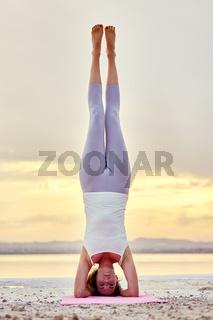 Woman doing Hatha yoga headstand or Sirsasana on nature