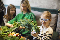 Family making christmas wreath from fir branches, christmas balls and pine cones on the wooden table