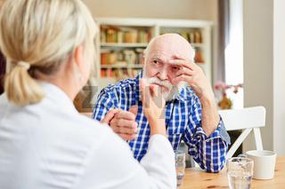 Ärztin tröstet einen Senior mit Depression