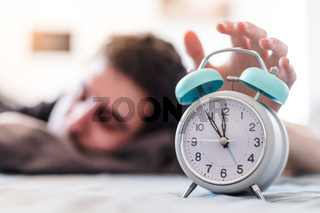 Alarm clock in the morning. Young wakes up in the blurry background.