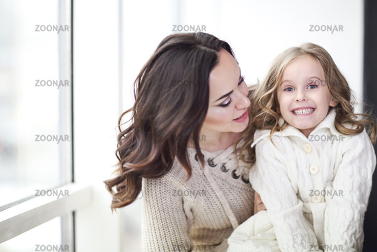 Mother and child daughter hugging by the window wearing cozy sweaters