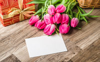 Beautiful bouquet from pink tulips and a gift on a table