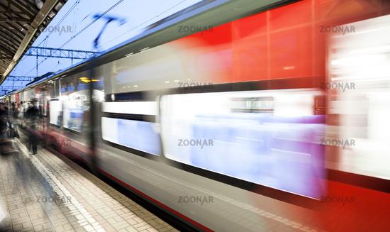 Motion blurred speed moving railroad train at railway station platform