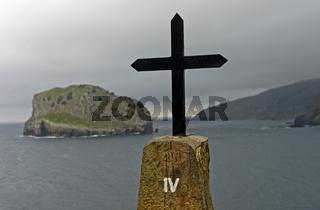 Schwarzes Metallkreuz auf einem Felsblock über der Bucht von Biskaya,Insel San Juan de Gaztelugatxe