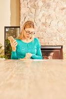 Frau liest ein Dokument mit Handy in der Hand