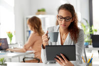businesswoman with tablet pc and coffee at office