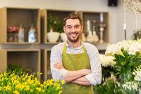 florist man or seller at flower shop counter