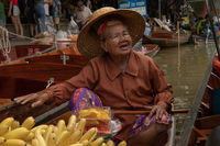 Woman selling bananas from floating market boat