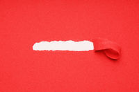 peel away ripped red paper to reveal hidden copy space underneath