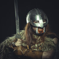 War, Viking, Scandinavian warrior with helmet and war paintings, wears a sword and a cape of animal skin