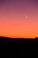 Sichelmond beim Sonnenuntergang vor rotem Himmel