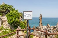 Sign with korean lettering, guide in engl. Candlestick Rock, korean Chotdaebawi. Donghae, Gangwon Province, South Korea, Asia.