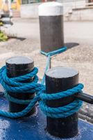 Mooring rope turned around bollard to secure ship at mooring - close-up