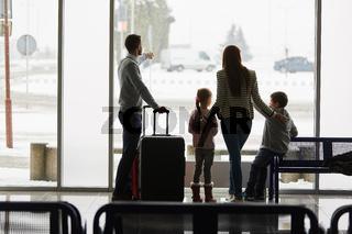 Familie und Kinder  warten auf Anschlussflug im Flughafen