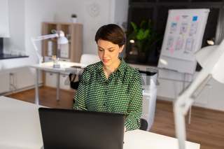 businesswoman working on laptop at night office