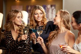 happy women clinking glasses at night club