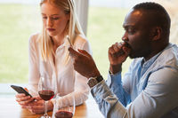 Junges Paar beim Dating abgelenkt vom Smartphone