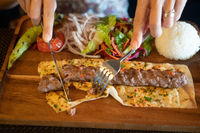 Closeup female hands eating kebab in Turkish restaurant